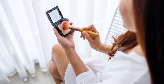 Closeup imagem de uma mulher bonita, aplicar maquiagem pó com pincel no quarto