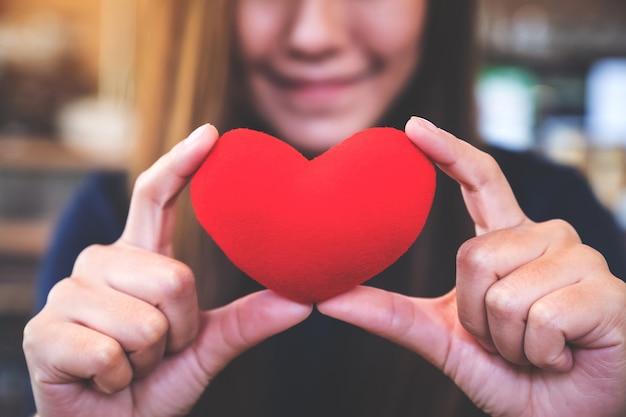 Closeup imagem de uma mulher feliz, segurando um cartaz de coração vermelho com sentimento apaixonado