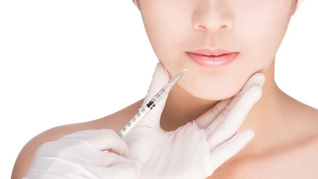 Closeup imagem de uma mulher. injeção nos lábios. isolado no branco, com trajeto de grampeamento