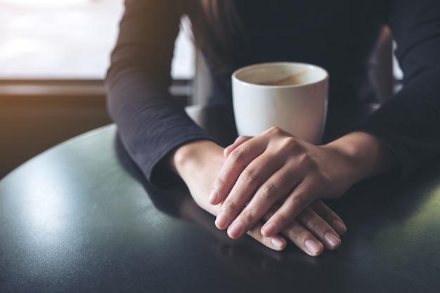 Closeup imagem de uma mulher segurando a mão e beber café quente no café