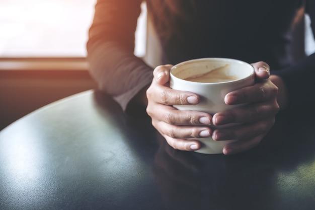 Closeup imagem de uma mulher segurando e beber café quente no café