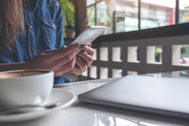 Closeup imagem de uma mulher segurando e usando o smartphone com copos de café e laptop na mesa de café