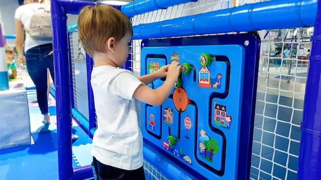 Closeup imagem do garotinho da criança resolvendo quebra-cabeça no palyground crianças no parque de diversões. conceito de crianças inteligentes e nova geração inteligente