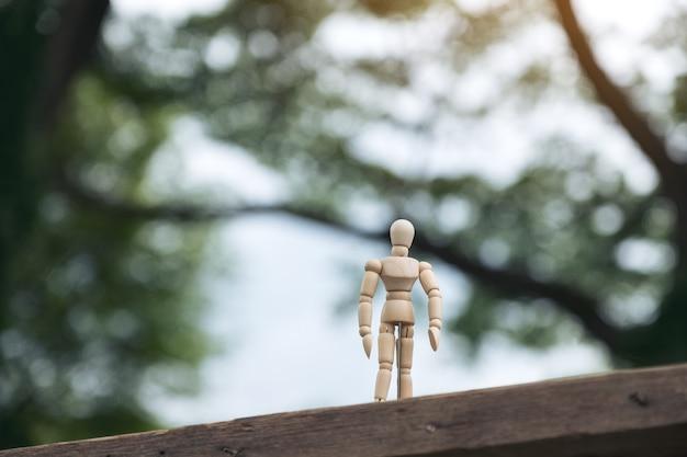Closeup imagem do modelo de figura de madeira de um homem em pé na mesa de madeira