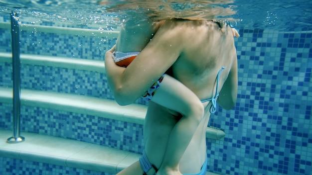 Closeup imagem subaquática de um menino pequeno com uma jovem mãe relaxando na piscina