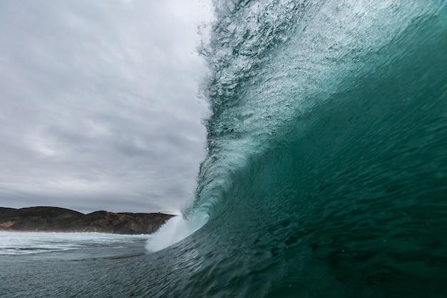 Closeup imagens das ondas do mar com montanhas sob um céu nublado em portugal