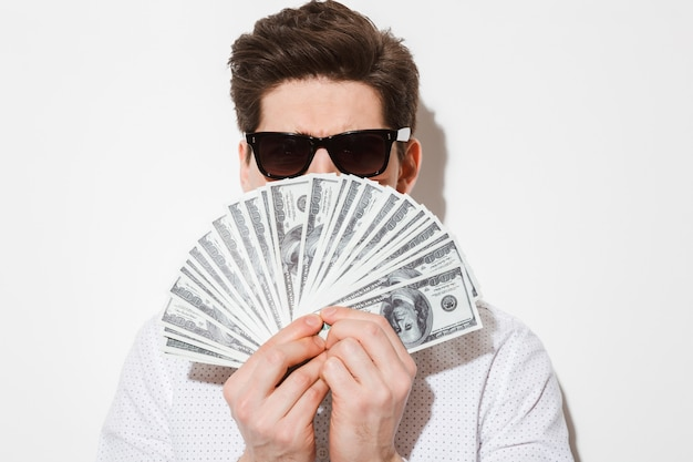 Closeup imagens de cara elegante de camisa casual e óculos de sol, cobrindo o rosto com muitas notas de dólar em dinheiro, isoladas sobre uma parede branca com sombra