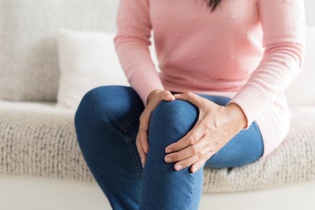 Closeup jovem mulher sentada no sofá e sentindo dor no joelho