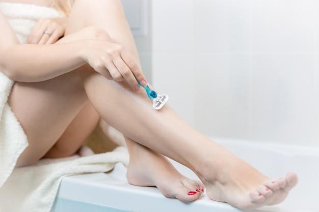 Closeup jovem sentada no banheiro e barbeando as pernas