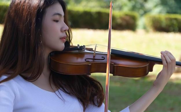 Closeup linda dama tocando violino com sentimento de interesse, retrato de modelo posando, luz embaçada ao redor