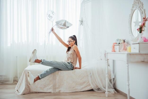 Closeup linda garota morena no, sorrindo amplamente e brincando com balões transparentes e prata. ela usa óculos e cabelo torcido.