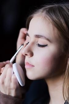 Closeup loira jovem preparado pelo maquiador
