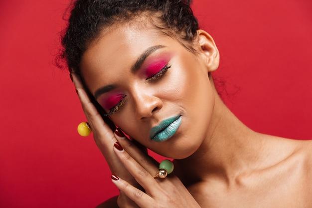 Closeup magnífica mulher afro-americana com maquiagem moda fechando os olhos e colocando a cabeça na palma da mão, muro vermelho