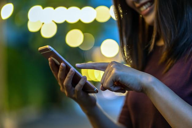 Closeup mão da mulher asiática usando smartphone e tela tocante no parque ao ar livre