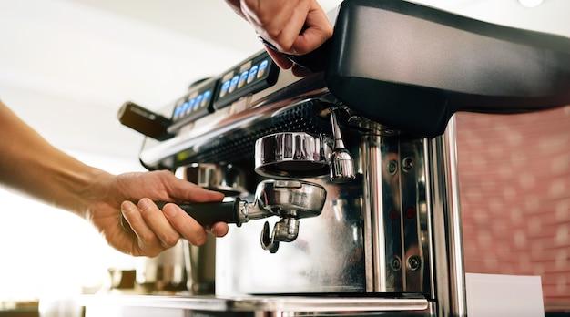 Closeup mão de barista insere o filtro de metal na máquina de café