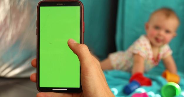 Closeup mão de fêmea anônima segurando smartphone com tela verde vazia