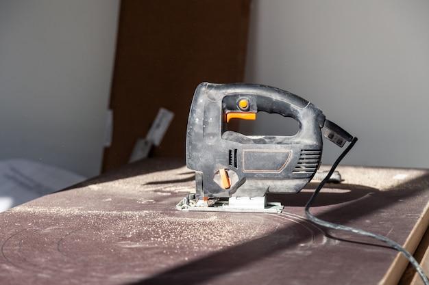 Closeup mão de marceneiro com ferramenta de corte profissional fretsaw ou serra de vaivém, corte a mesa de madeira, tábua de serrar, limalha marrom, serragem. cortar um buraco para a pia no banheiro