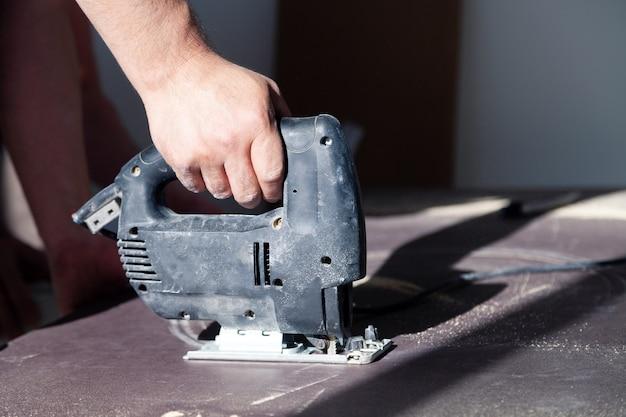 Closeup mão de marceneiro com ferramenta de corte profissional fretsaw ou serra de vaivém, corte a mesa de madeira, tábua de serrar, limalha marrom, serragem. faça um buraco para a pia na cozinha