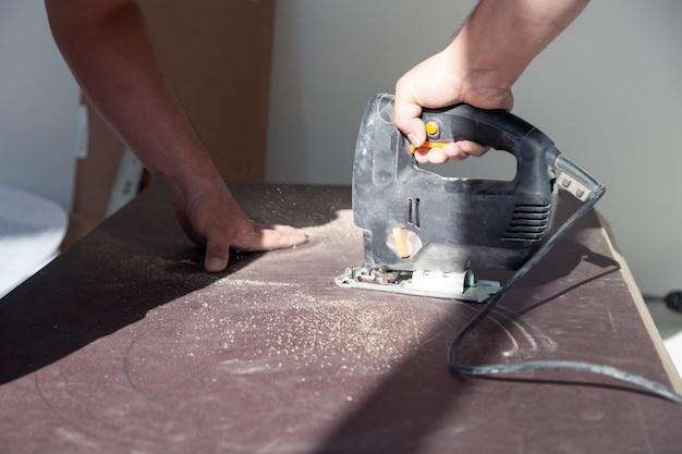 Closeup mão de marceneiro com ferramenta de corte profissional fretsaw ou serra de vaivém, corte a mesa de madeira, tábua de serrar, limalha marrom, serragem. instalação e reparo profissional