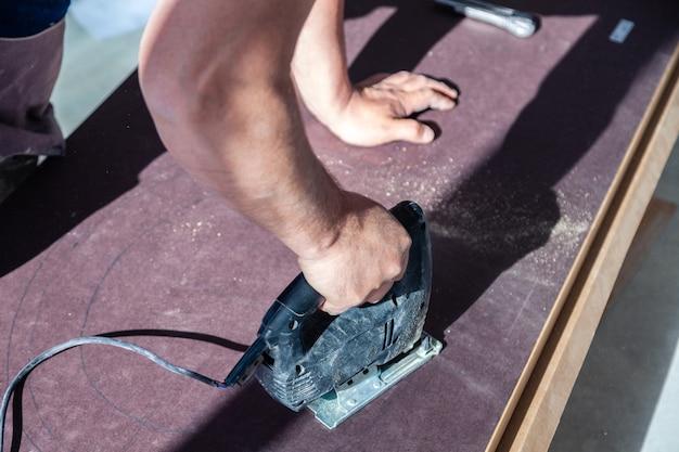 Closeup mão de marceneiro com fretsaw de ferramenta de corte profissional