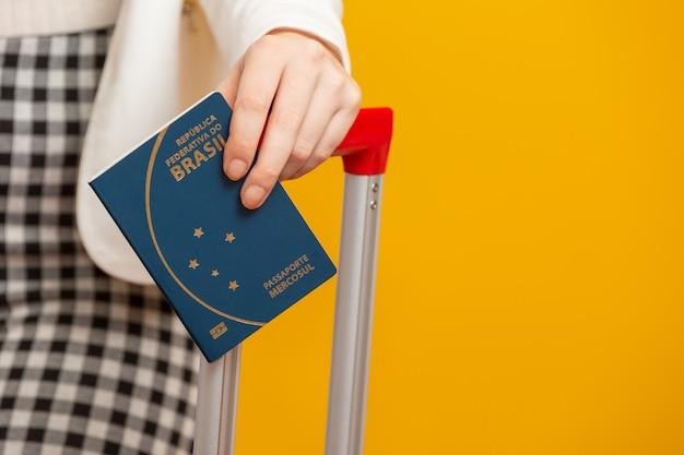 Closeup mão de menina segurando um passaporte brasileiro. em amarelo.