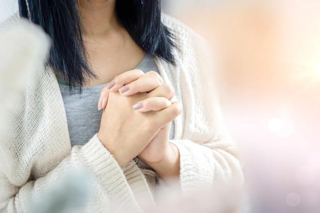 Closeup mão de mulher cristã orando pela bênção de deus, espiritualidade, religião e conceito de crença em deus