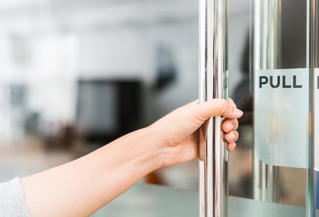 Closeup mão de mulheres abre a maçaneta da porta