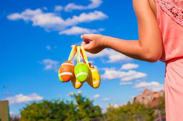 Closeup mão de uma menina segurando ovos de páscoa coloridos fundo do céu azul