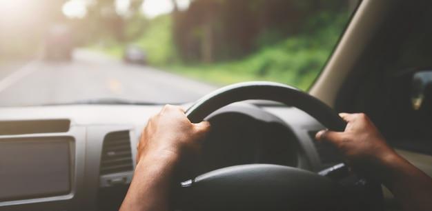 Closeup mão do carro do motorista na estrada com luz do sol