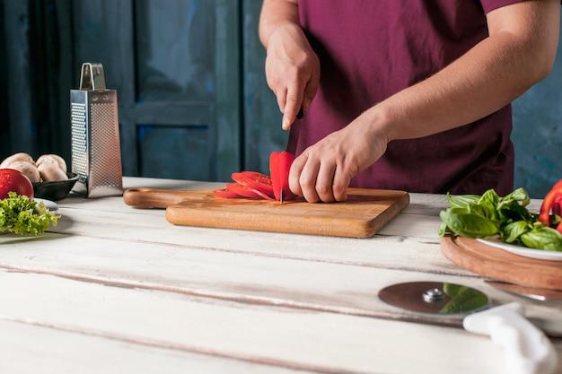 Closeup mão do chef padeiro fazendo pizza na cozinha