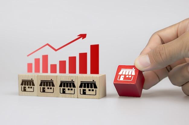 Closeup mão e blocos de brinquedo de cubo de madeira com ícones de loja de negócios de franquia
