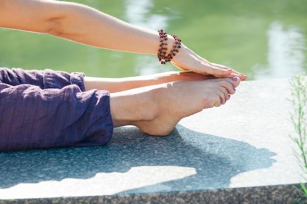 Closeup mão feminina segurando o pé, esticando a pose