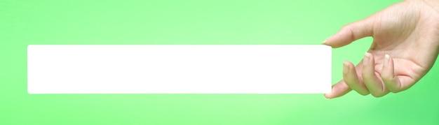 Closeup mão feminina vazia segurando alguns como um cartão de visita longo em branco sobre fundo verde.