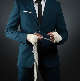 Closeup mão masculina do lutador empresário de terno com bandagens e punhos cerrados.