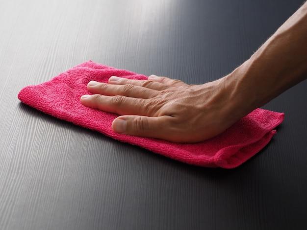 Closeup mão masculina segurando o pano de microfibra rosa para limpar a mesa.