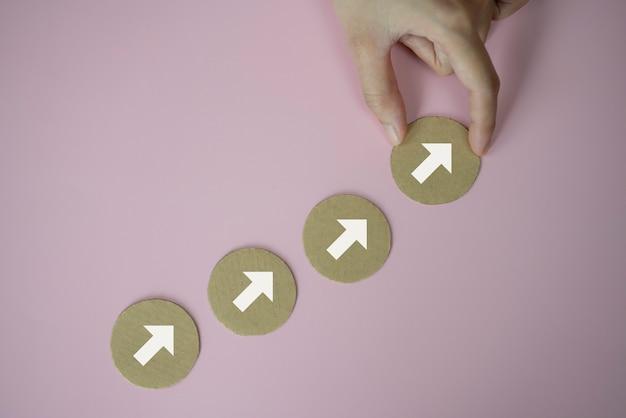 Closeup mão organizando empilhamento de corte de papel como escada de degraus com o símbolo de seta para cima