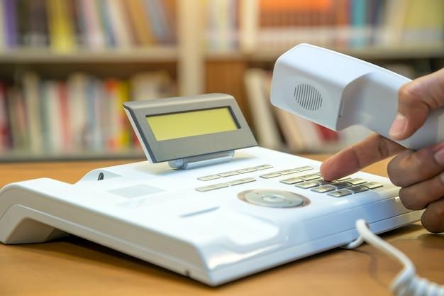 Closeup mão pega o telefone e aperta o botão