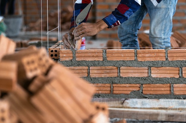 Closeup mão profissional trabalhador da construção civil colocar tijolos no novo site industrial