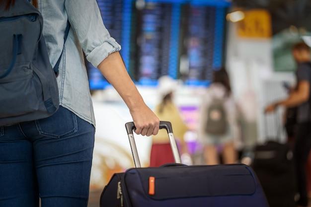 Closeup mão segurando a bagagem sobre a placa de vôo para o check-in na informação do voo