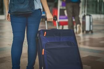 Closeup mão segurando a bagagem sobre a placa de voo para o check-in no voo informat