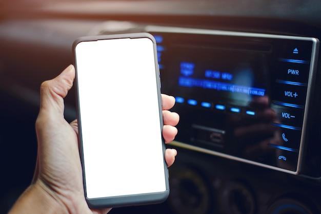 Closeup mão segurando um smartphone e o bluetooth está conectado, tocando música no carro.
