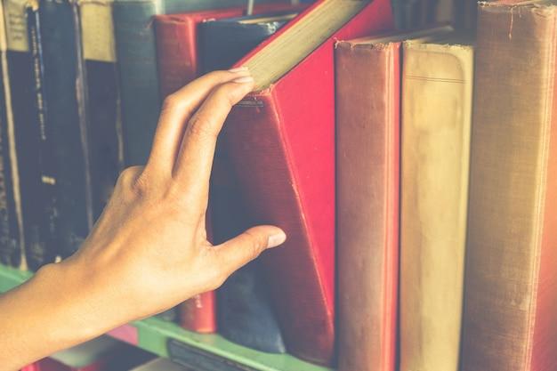 Closeup mão selecionando livro de uma estante de livros