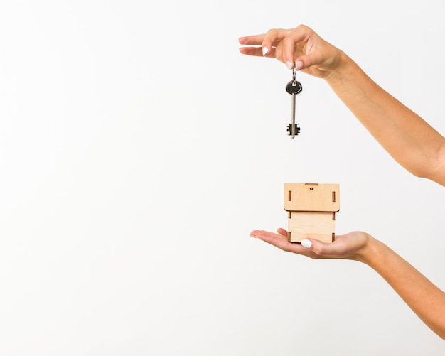 Closeup mãos com chave e uma casa de campo