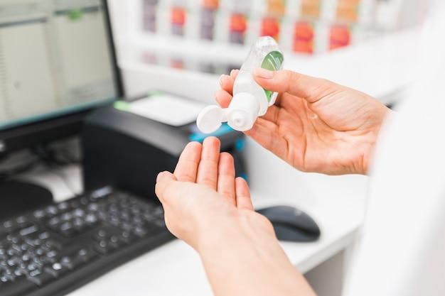Closeup mãos de um caixa usando desinfetante na frente da caixa de dinheiro na loja depois de receber dinheiro.