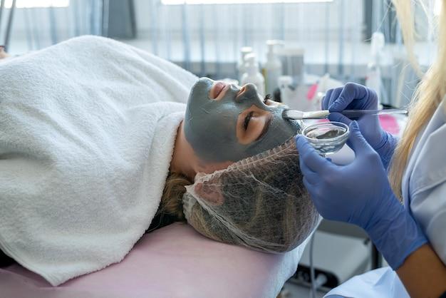 Closeup mãos de uma esteticista com luvas azuis aplicando máscara de beleza no rosto de uma cliente