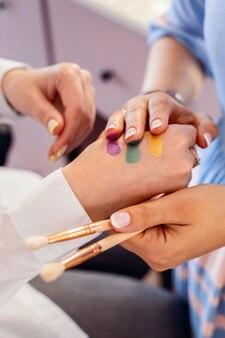 Closeup mãos de uma visagista profissional aplicando amostras coloridas de sombras da moda