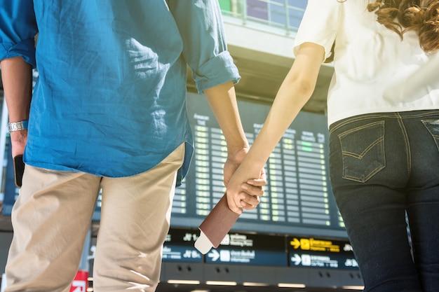 Closeup mãos do casal asiático segurando o passaporte