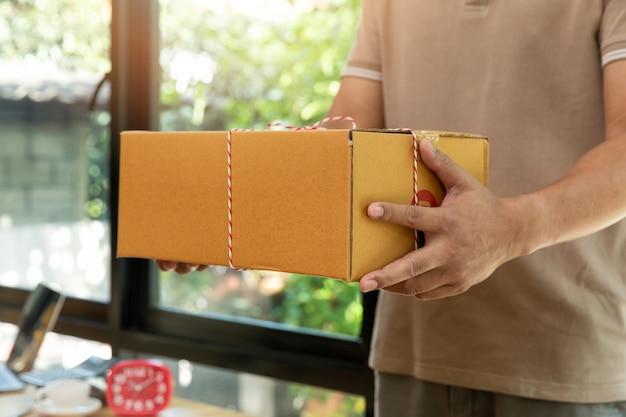 Closeup mãos do entregador segurando pacote de pacote para entregar