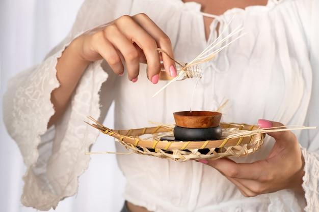 Closeup: mãos femininas com delicada manicure rosa despeje o óleo em um pires para fazer uma massagem. massagem tailandesa com pedras. spa & cuidados