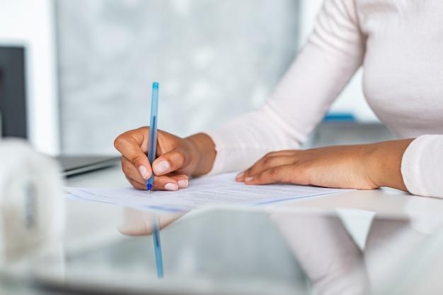 Closeup mãos femininas durante a escrita com caneta em um papel, mulher de negócios, assinando um documento